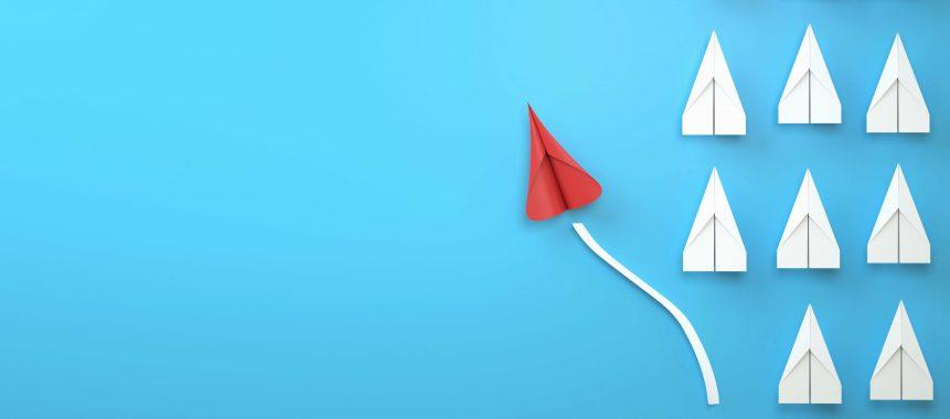 Bild zeigt symbolisches Changemangement: Rote Papierflugzeug reiht sich aus anderen Papierfliegern aus