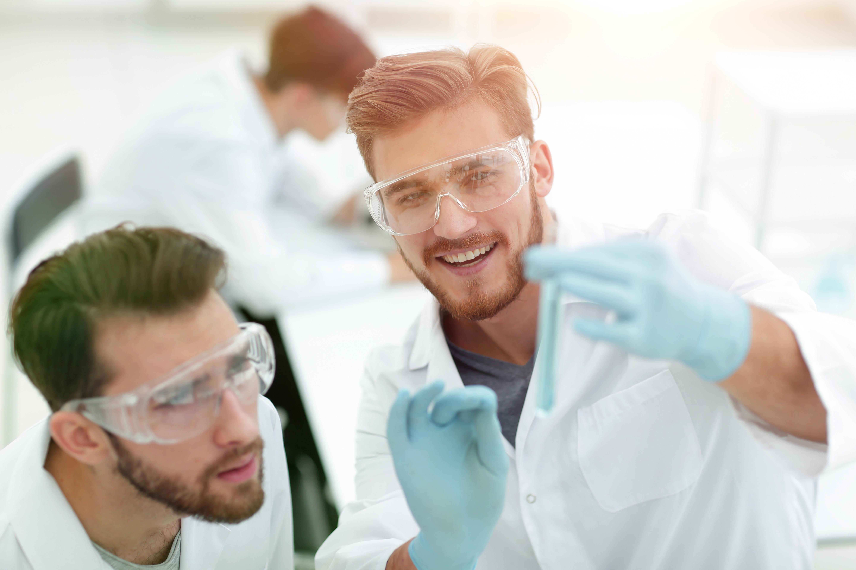 Bild zeigt zwei Mitarbeiter im Chemielabor, die sich auch in Zeiten des Fachkräftemangel in Chemie- und Pharmabranche für diesen Bereich entschieden haben