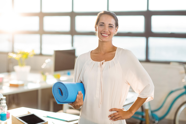 Bild zeigt Mitarbeiterin mit Yogamatte, die mit Hilfe von Betrieblichem Gesundheitsmanagement ihre Resilienz stärkt