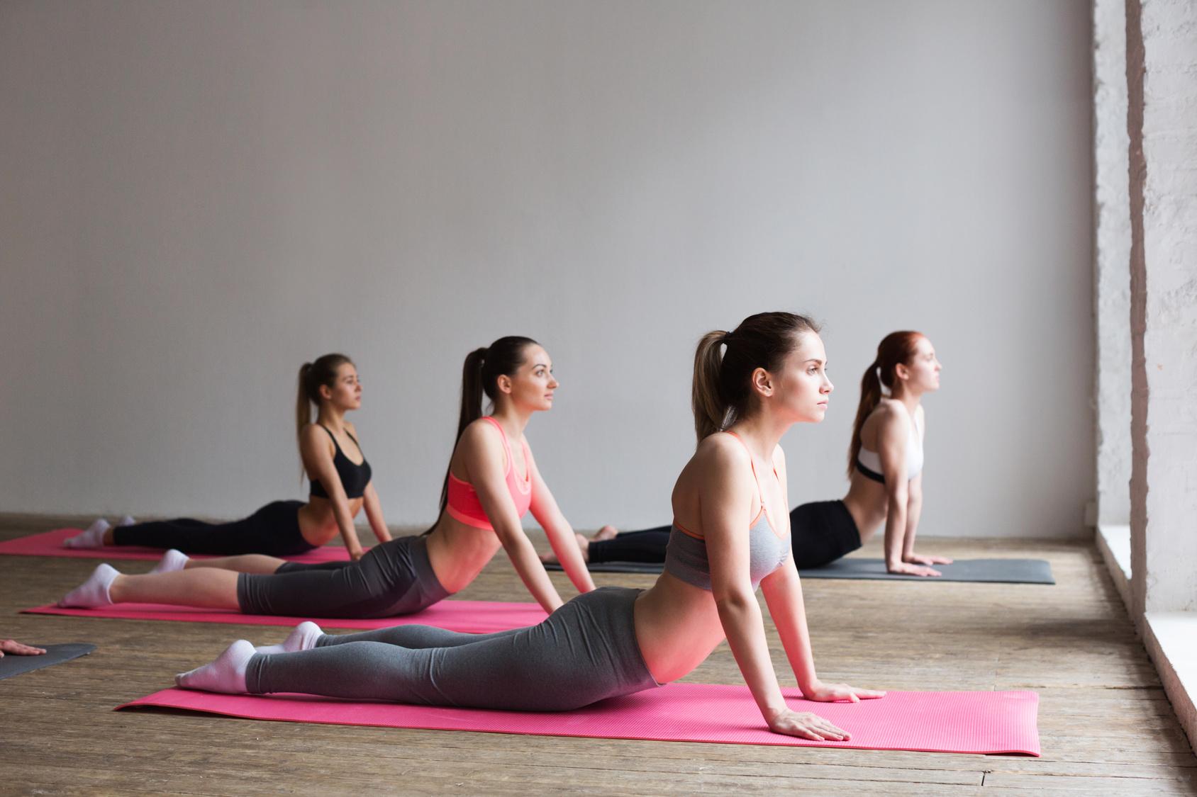 Bild zeigt Mitarbeiter, die Gesundheitsförderung und Prävention im Yogastudio betreiben, um ihre Resilienz zu stärken