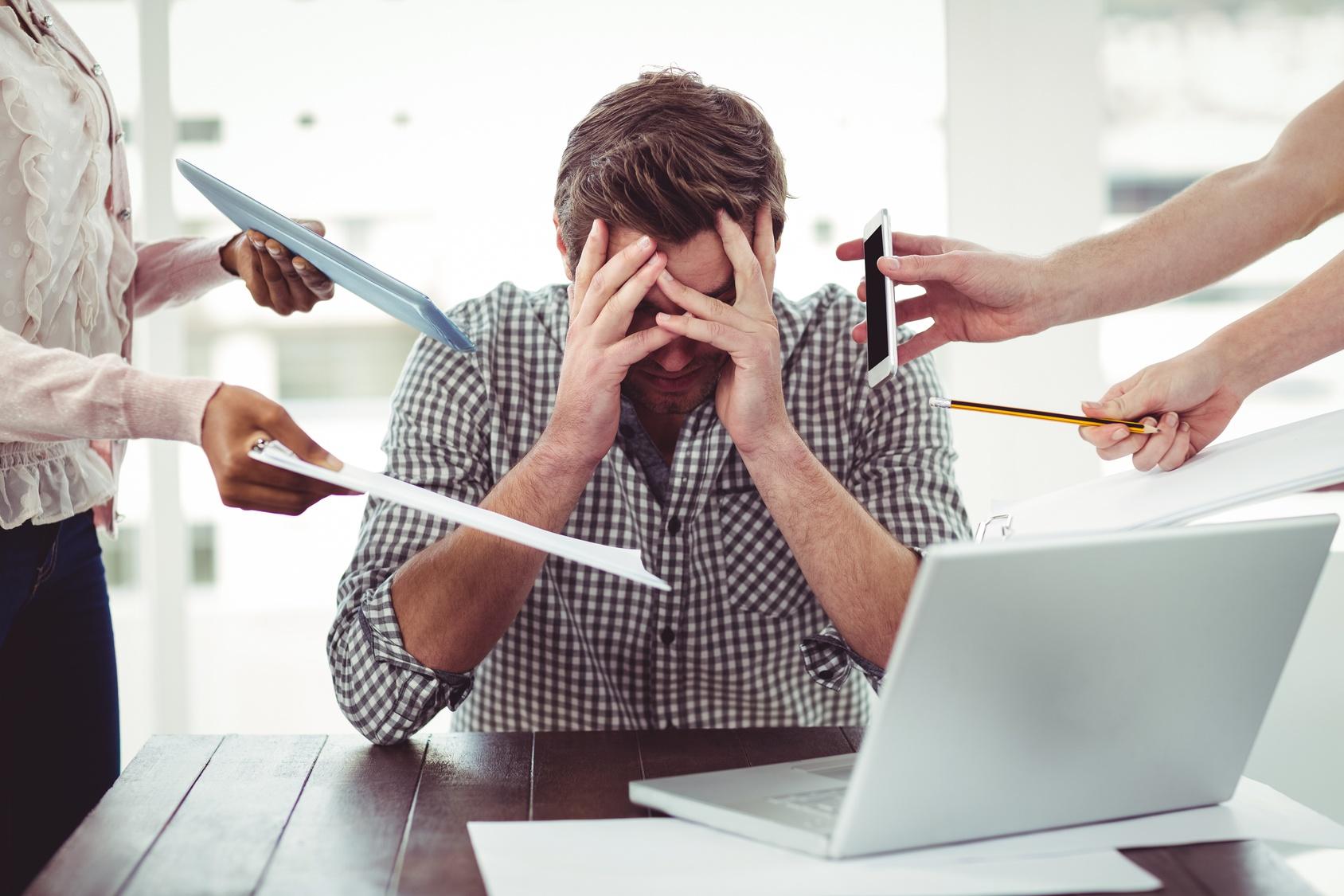Bild zeigt gestressten Mitarbeiter mit vielen Aufgaben