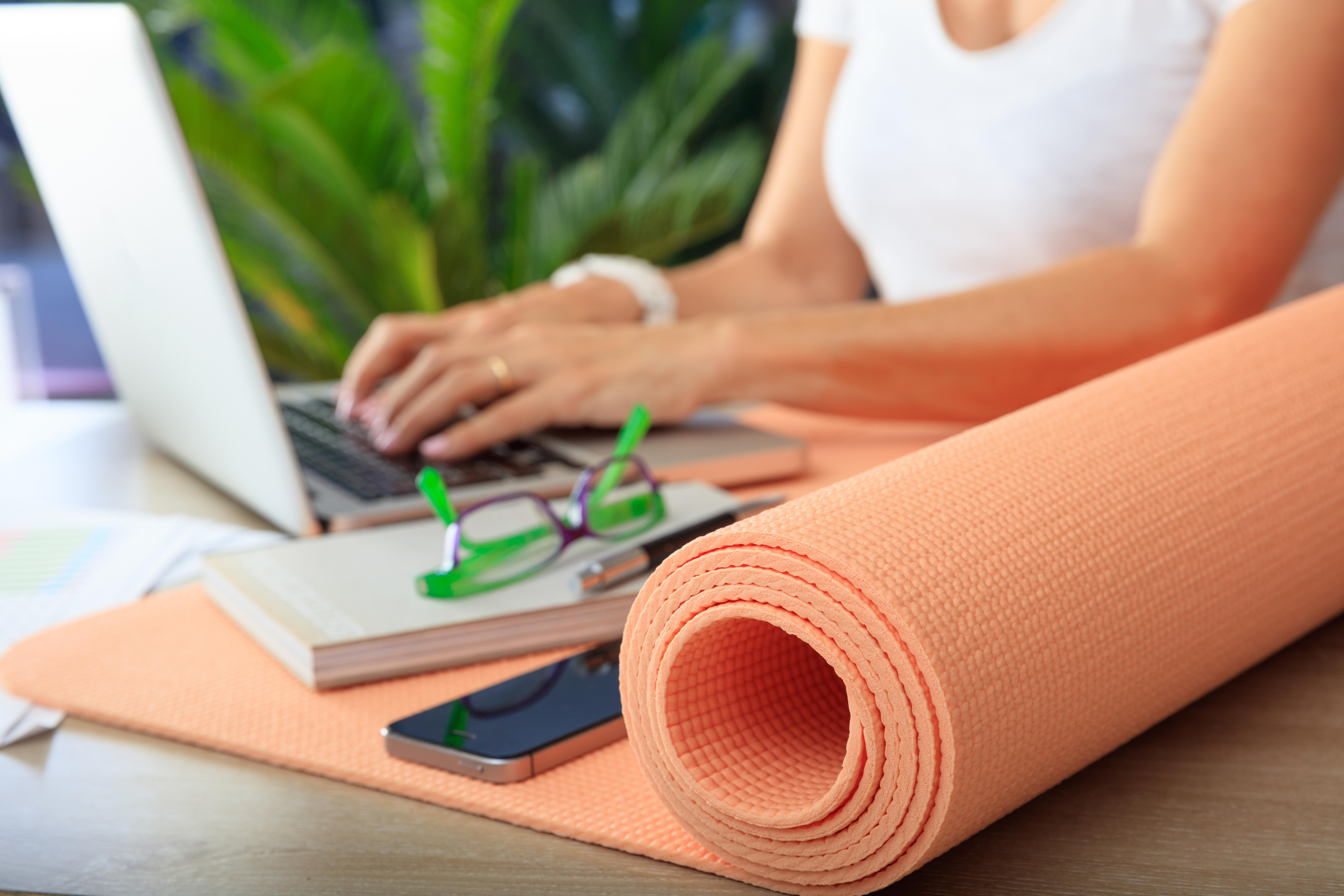 Bild zeigt Frau mit Yogamatte und PC am Schreibtisch und steht symbolisch für gesunde Führung und Betriebliches Gesundheitsmanagement