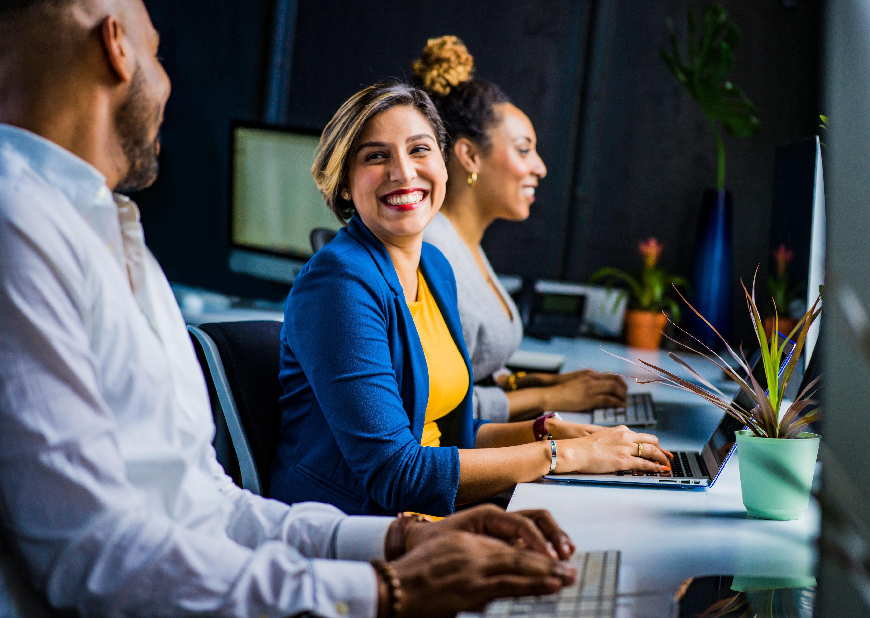 Bild zeigt lachende Frau am Computer mit Kollegen