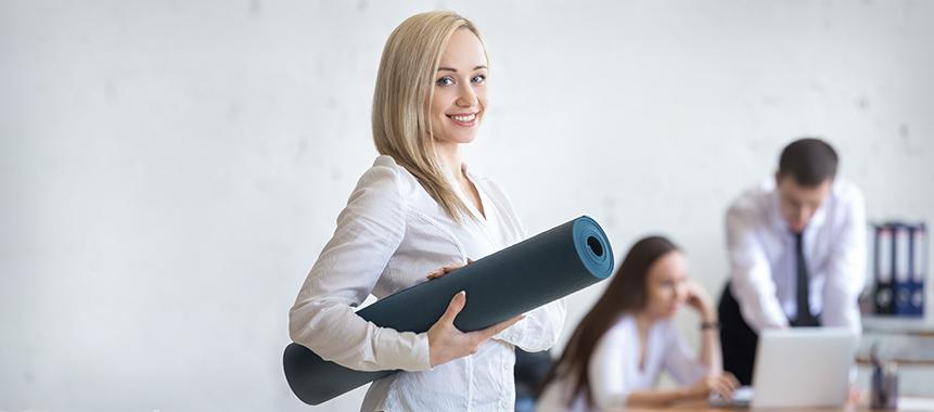 Bild zeigt glückliche junge Mitarbeiterin, die Yoga im Rahmen der betrieblichen Gesundheitsförderung nutzt